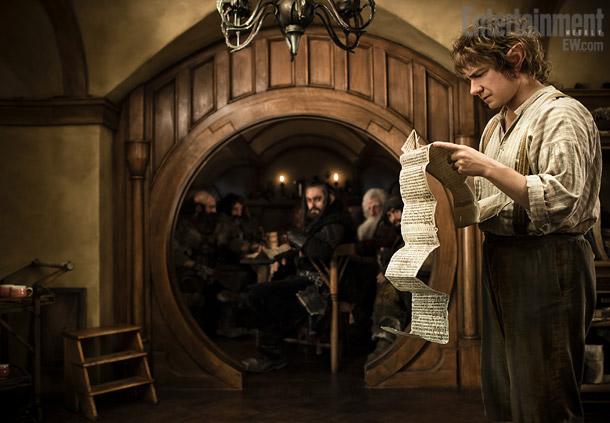 Bilbo Bolsón lee detenidamente ante la atenta mirada de los enanos que se han colado en su casa