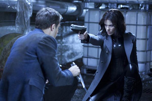 Selene con traje de cuero látex, chaquetón y pistola