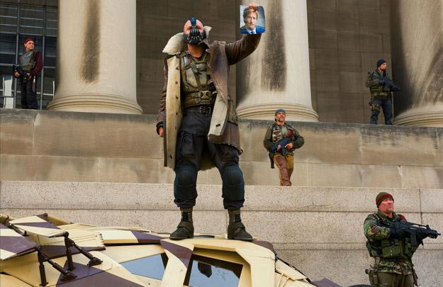 Bane y su grupo de terroristas se ríen del caballero blanco de Gotham... el fallecido Harvey Dent